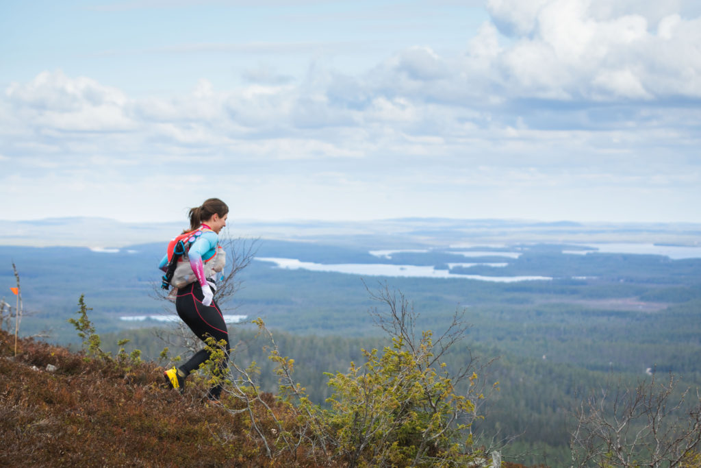 A female runner is going downhill, there's a fell scenery with few lakesin in the backround